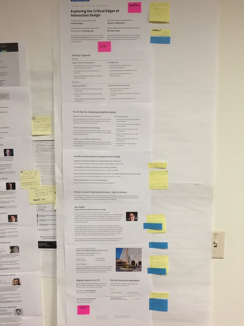 Paper prototypes hung on a wall marked up with critique on Post-in notes.